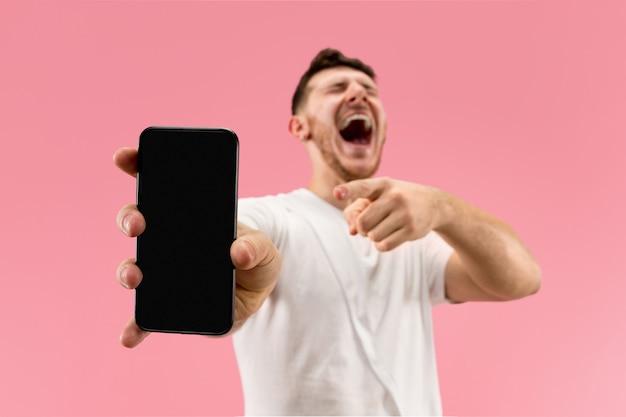 Молодой красавец показывает экран смартфона на розовом фоне с удивленным лицом. человеческие эмоции, концепция выражения лица. модные цвета