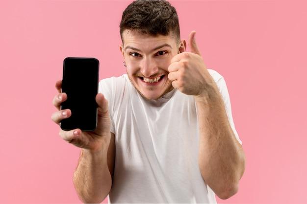 Giovane uomo bello che mostra lo schermo dello smartphone su rosa con una faccia a sorpresa
