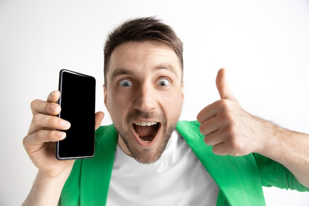 スマートフォンの画面を示す若いハンサムな男