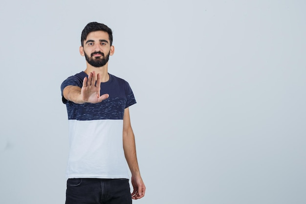 Молодой красавец показывает жест стоп