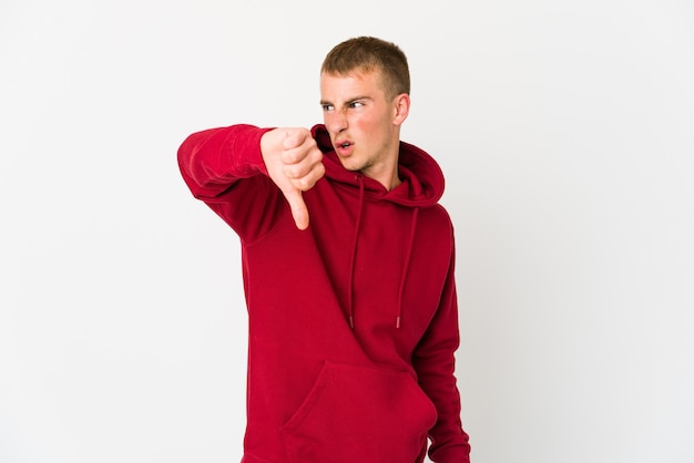 親指を下に向けて嫌悪感を表現する若いハンサムな男