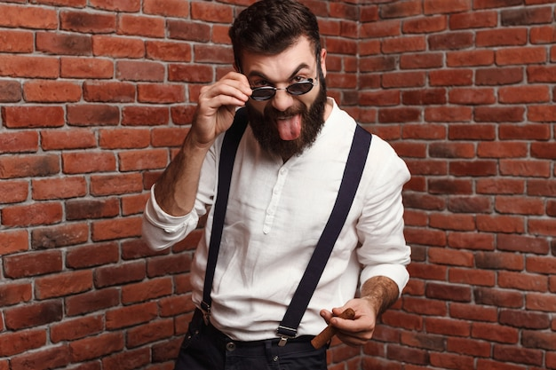 Young handsome man showing tongue holding cigar on brick wall.