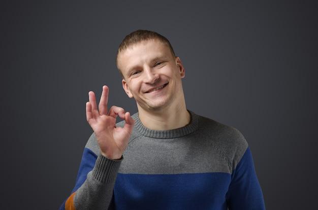 若いハンサムな男はジェスチャー「ok」を示しています。黒い表面のスタジオでの感情的な写真。