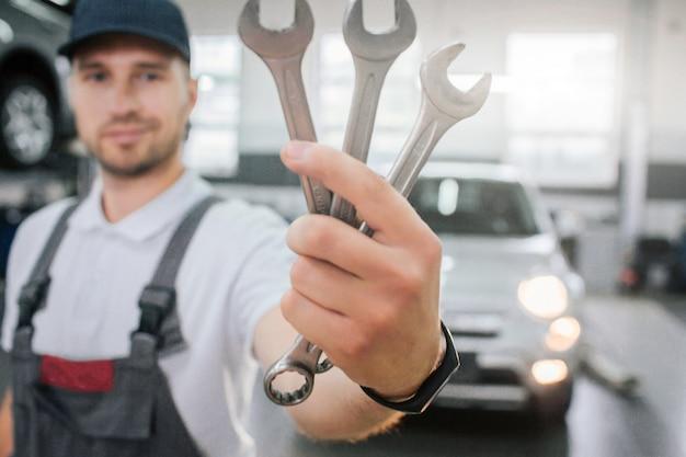 Молодой красавец показывает набор гаечных ключей. он смотрит на них и улыбается. парень носит форму. он стоит перед белой машиной. молодой человек немного улыбается.