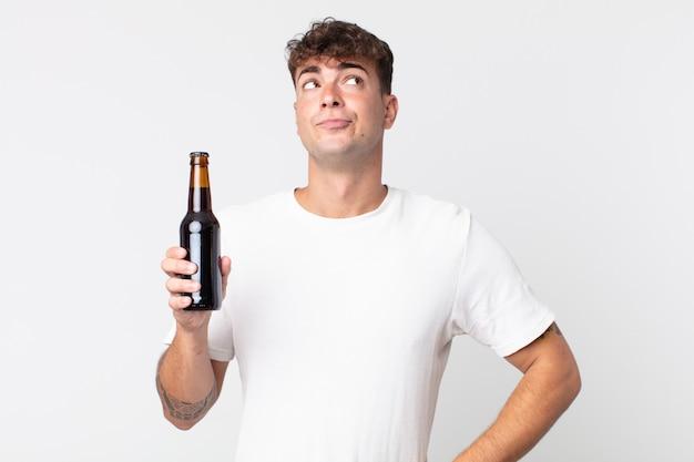 肩をすくめる、混乱して不確かな感じ、ビール瓶を持っている若いハンサムな男