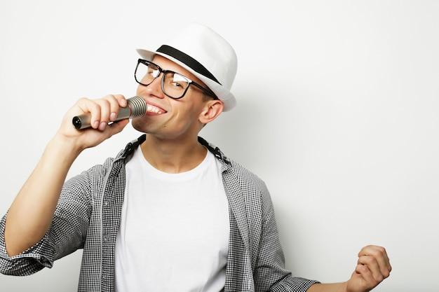 Молодой красавец поет с микрофоном
