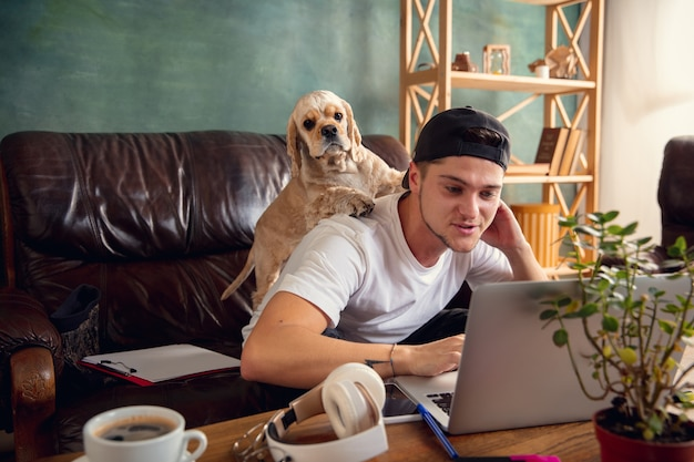 Young handsome man sitting on brown sofa and working with his cute dog