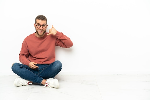 Young handsome man sitting on the floor making phone gesture. call me back sign