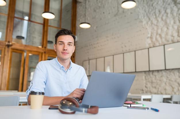 Молодой красавец сидит в офисе открытого пространства, работая на ноутбуке