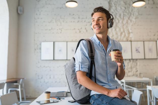 Молодой красавец сидит за столом в наушниках с рюкзаком в коворкинг-офисе, пьет кофе