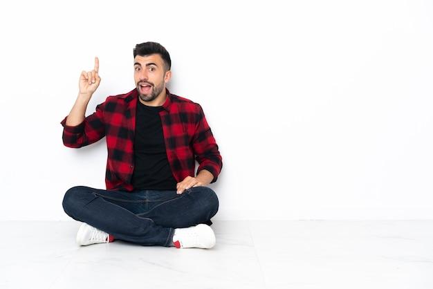 指を持ち上げながら解決策を実現しようと床に座っている若いハンサムな男