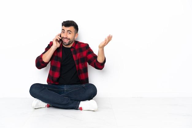 누군가와 휴대 전화로 대화를 유지하는 바닥에 앉아 젊은 잘 생긴 남자