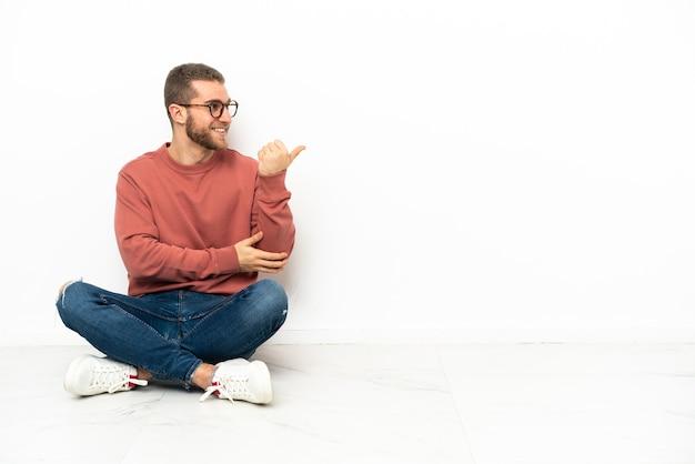 제품을 제시하기 위해 측면을 가리키는 바닥에 앉아 젊은 잘 생긴 남자