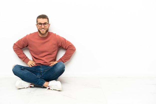 엉덩이에 팔을 포즈와 미소 바닥에 앉아 젊은 잘 생긴 남자