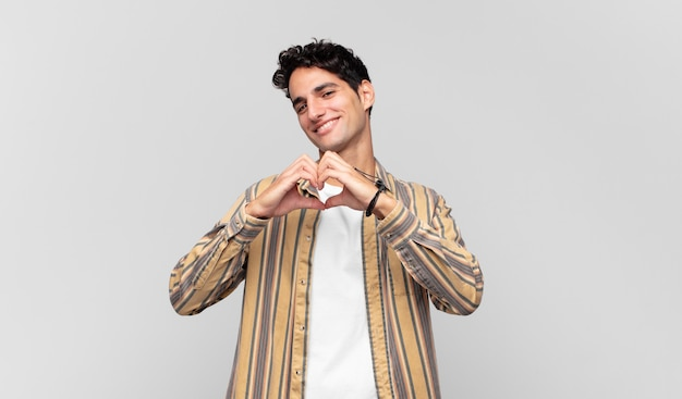 웃고 행복하고 귀엽고 낭만적이고 사랑에 빠진 젊은 잘 생긴 남자, 양손으로 하트 모양 만들기