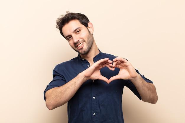 若いハンサムな男は笑顔で幸せ、かわいい、ロマンチックな恋を感じ、両手でハートの形を作ります