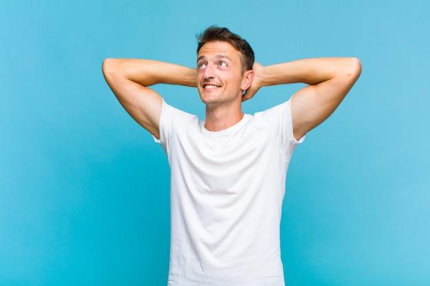Молодой красивый мужчина улыбается и чувствует себя расслабленным, довольным и беззаботным, позитивно смеется и пугает