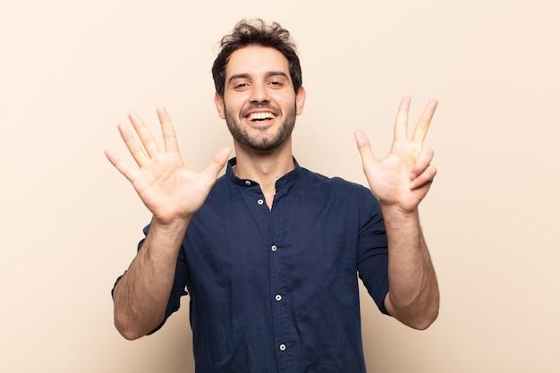 若いハンサムな男は笑顔でフレンドリーに見え、前に手を前に8番または8番を示し、カウントダウン