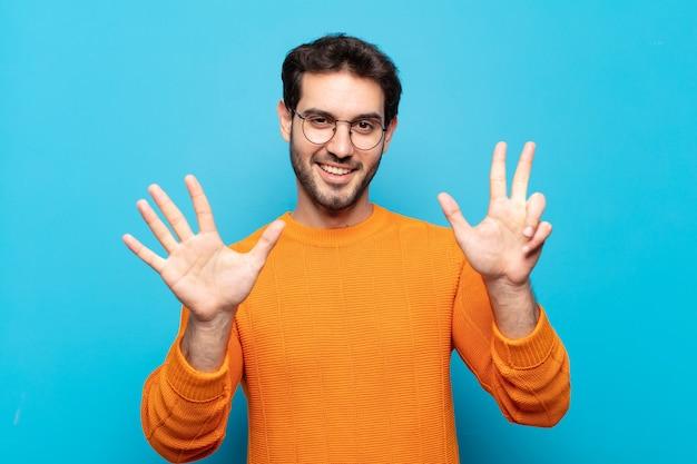 젊은 잘 생긴 남자가 미소하고 친절하게보고, 앞으로 손으로 8 또는 8 번째를 보여주는 카운트 다운