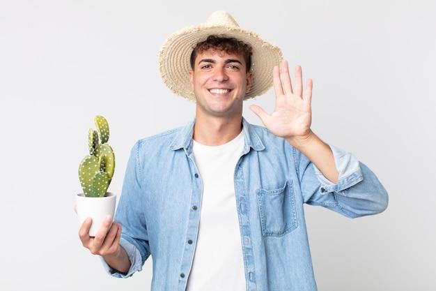 若いハンサムな男は笑顔でフレンドリーに見え、5番を示しています。装飾的なサボテンを持っている農夫 Premium写真