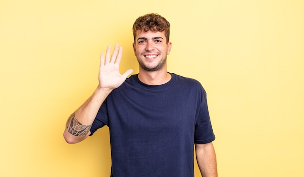 Молодой красивый мужчина улыбается и выглядит дружелюбно, показывает номер пять или пятое с рукой вперед, отсчитывая