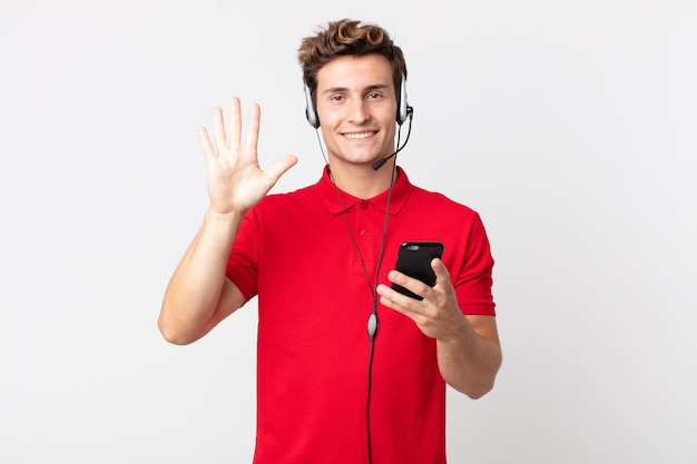 笑顔でフレンドリーに見える若いハンサムな男、スマートフォンとヘッドセットで5番を示しています