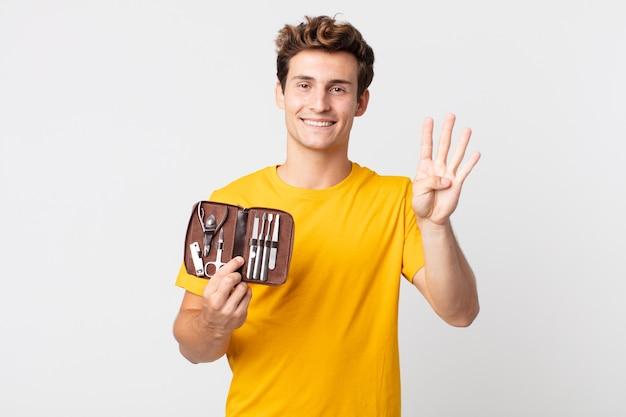 Молодой красивый мужчина улыбается и выглядит дружелюбно, показывает номер четыре и держит футляр для инструментов для ногтей