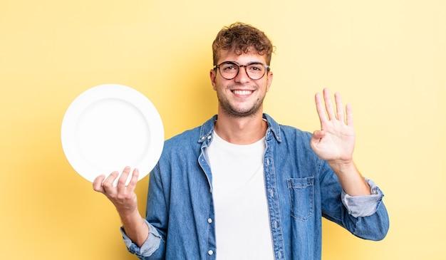 Молодой красивый мужчина улыбается и выглядит дружелюбно, показывая номер четыре. концепция пустого блюда