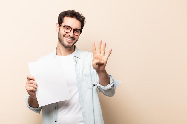 Молодой красивый мужчина улыбается и выглядит дружелюбно, показывает номер четыре или четвертый с рукой вперед, отсчитывая