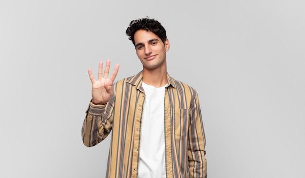 若いハンサムな男は笑顔でフレンドリーに見え、前に手を前に4番目または4番目を示し、カウントダウン