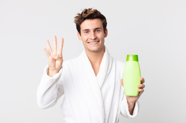 若いハンサムな男は笑顔でフレンドリーに見え、バスローブで4番を示し、シャンプーボトルを持っています