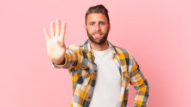 Молодой красивый мужчина улыбается и выглядит дружелюбно, показывая номер четыре