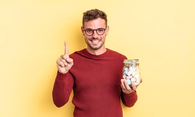若いハンサムな男は笑顔でフレンドリーに見え、ナンバーワンを示しています。ゼリーキャンディーのコンセプト