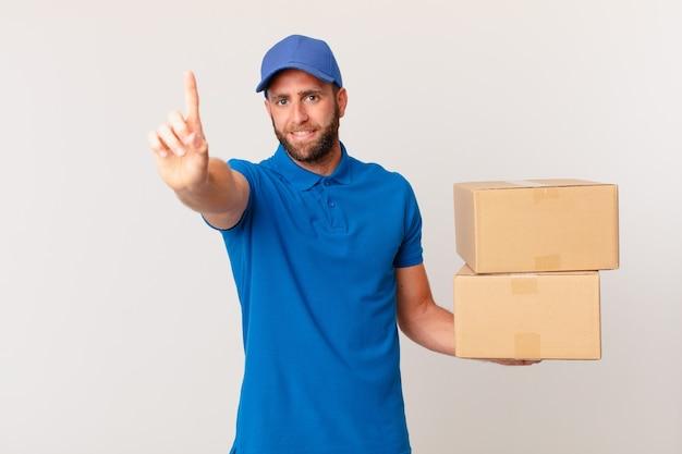 Молодой красивый мужчина улыбается и выглядит дружелюбно, показывая номер один. концепция доставки пакетов