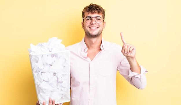 Молодой красивый мужчина улыбается и выглядит дружелюбно, показывая номер один. бумажные шары мусор концепция