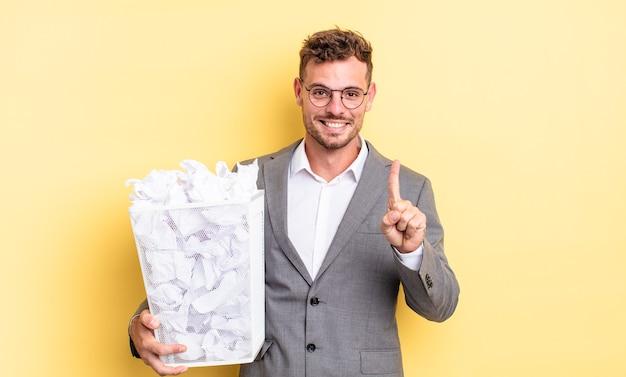 Молодой красивый мужчина улыбается и выглядит дружелюбно, показывая концепцию мусора бумажных шариков номер один