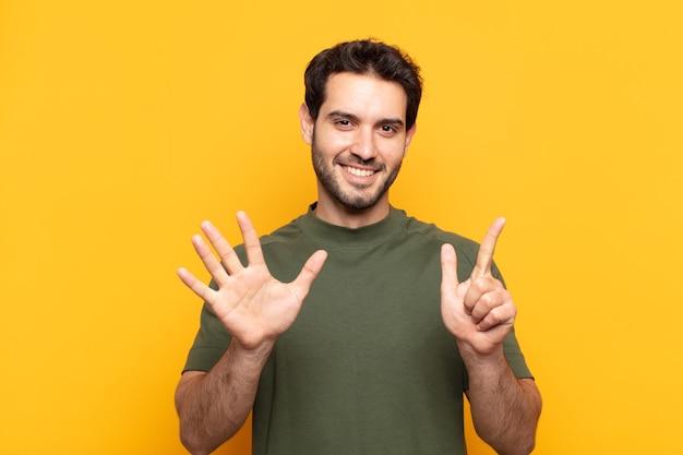 若いハンサムな男は笑顔でフレンドリーに見え、前に手を前に7番または7番を示し、カウントダウン
