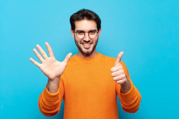 Молодой красивый мужчина улыбается и выглядит дружелюбно, показывает номер шесть или шестой рукой вперед, отсчитывая