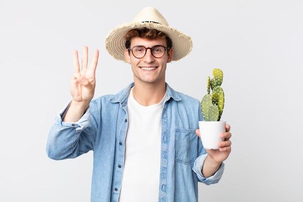若いハンサムな男は笑顔でフレンドリーに見え、3番目を示しています。装飾的なサボテンを持っている農夫