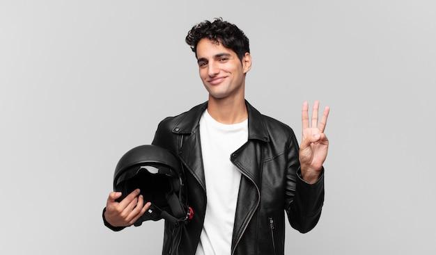 若いハンサムな男は笑顔でフレンドリーに見え、手を前に向けて3番目または3番目を示し、カウントダウンします。バイクライダーのコンセプト