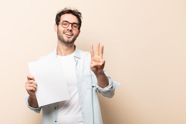若いハンサムな男は笑顔でフレンドリーに見え、前に手を前に3番目または3番目を示し、カウントダウン