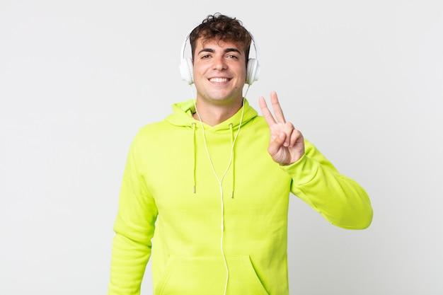 Молодой красивый мужчина улыбается и выглядит дружелюбно, показывая номер два и наушники