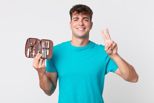 Молодой красивый мужчина улыбается и выглядит дружелюбно, показывает номер два и держит ящик для гвоздей