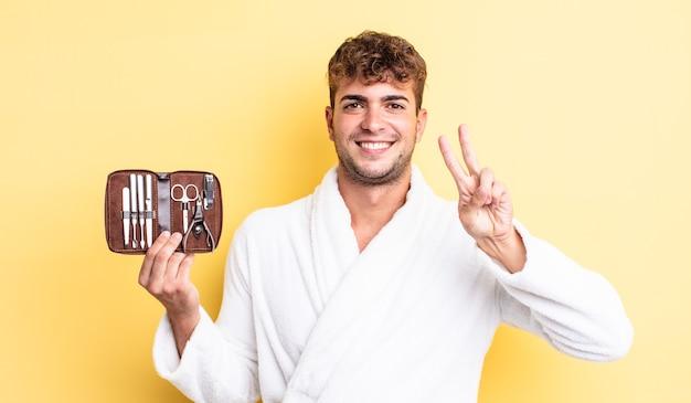 Молодой красивый мужчина улыбается и выглядит дружелюбно, показывая номер два. гвозди инструменты футляр концепция