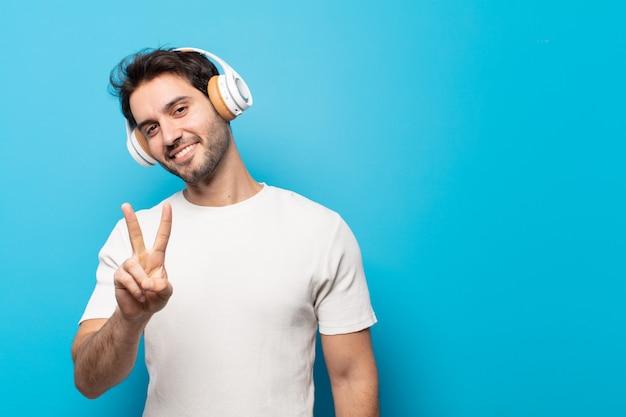 若いハンサムな男は笑顔でフレンドリーに見え、前に手を前に2番目または2番目を示し、カウントダウン