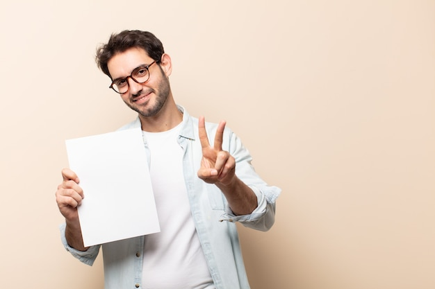 笑顔で幸せそうに見える若いハンサムな男、のんきで前向きで、片手で勝利または平和を身振りで示す