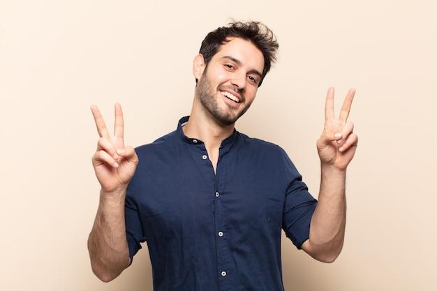 Молодой красивый мужчина улыбается и выглядит счастливым, дружелюбным и довольным, жестикулирует победу или мир обеими руками