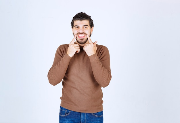 若いハンサムな男は笑顔で歯を見せるために口を指しています。高品質の写真