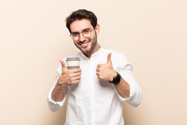 두 엄지 손가락으로 광범위하게 행복하고 긍정적이며 자신감 있고 성공한 찾고 웃는 젊은 잘 생긴 남자
