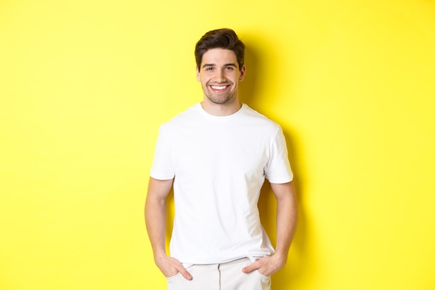 Young handsome man smiling at camera, holding hands in pockets, standing against yellow background.